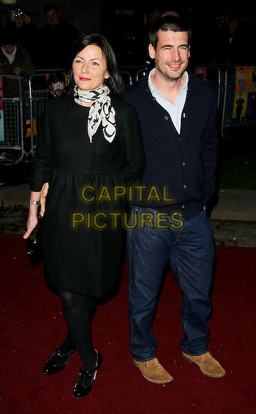 "DAVINA McCALL & MATTHEW ROBERTSON.""The Boat That Rocked"" world film premiere at The Odeon, Leicester Square, London, England..March 23rd, 2009.full length black dress white print scarf t-bar patent shoes bow clutch bag jeans denim blue navy jacket top sweater  married husband wife.CAP/CAN.©Can Nguyen/Capital Pictures."