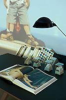 "The desk has an integrated bookshelf and displays four tiny sculptural glass vitrines whilst the Celine Duval video installation ""Horizon IV""  may be seen in the background"