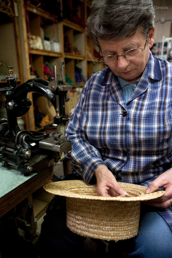 9 december 2009 - Coustilleres' hat factory, Septfonds, France - Michele Lorente works at the Coustilleres' hat factory since 15 years. She trims a ribbon on a straw hat at the Coustilleres' hat factory. She is using specially-designed antique sewing machines. The sewing machines are powered by the women's feet operating two treadles..Septfonds is the heart of French straw hat making, due to its very ancient hatter tradition. The hat making industry had its commercial peak in the late 19th century..Coustillères is a family owned hat making factory that has been making straw hats in Septfonds for nearly 100 years. They make hats from straw, felt, and cloth as well as caps. The current owner is Jean-Claude Coustilleres. He is one of the last hat makers of the region..The straw hat making process is very labor intensive and numerous hands are involved. Nearly all of the equipment is over 100 years old, they use the original presses and tools including aluminium molds and sewing machines and dye their own straw continuing the traditional methods of manufacturing. The hat blocking and shaping, straw braids construction and dyeing are all done by hand..The company works on behalf of fashion houses and makes a variety of regional and historical hats. It produces 2 collections a year distributed by a network of salespeople and through a catalog to clients around the world. Photo credit: Benedicte Desrus
