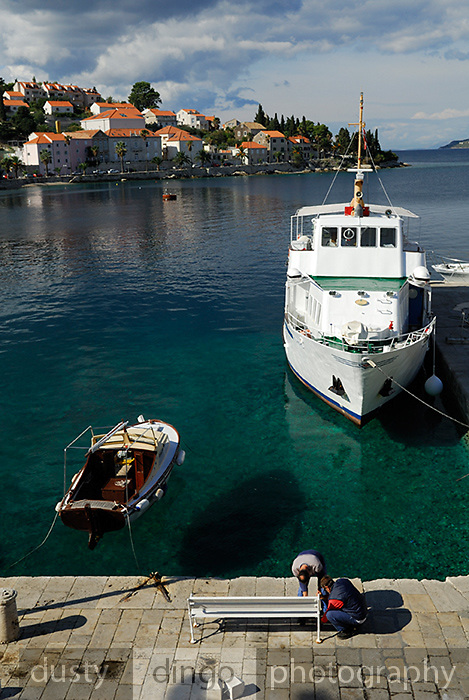 Boats moored at small harbour, two men reparing bench in foreground. Korcula old town, island of Korcula, Croatia