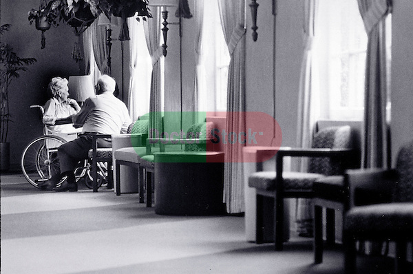 elder couple conversing in nursing home
