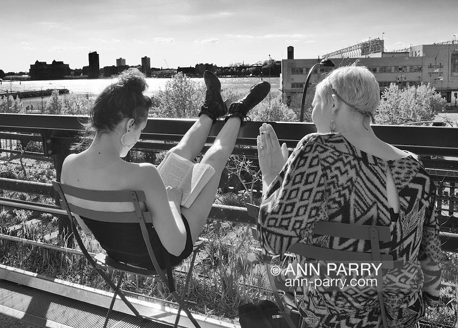 Woman reading at the High Line, Manhattan, with Hudson River and New Jersey in background, New York, April 27, 2013