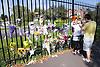 People placing memorial flowers on railings,