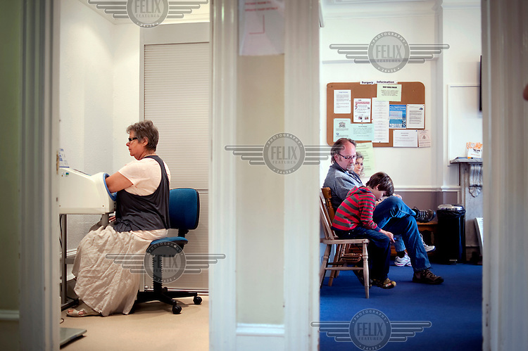 Patients wait for treatment at Dukes Avenue Practice, an NHS doctor's surgery in North London. On the left a patient self checks her blood pressure.