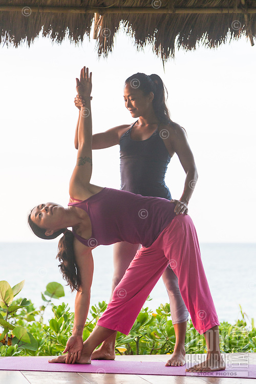 Yoga instructor Miki Sato assists a student with the triangle yoga asana on a beach in Hawai'i.