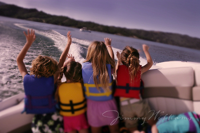 Four kids put their hands up in the air to feel the wind blowing as they take a fun boat ride through a lake