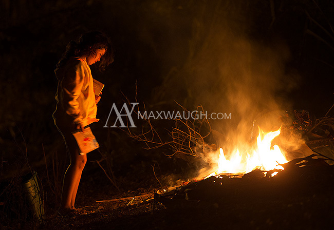 A girl burns trash near the road.