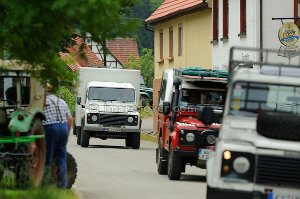 Germany, Land Rover Classic Club 2005. Some Land Rover Defenders passing through a small village. --- No releases available. Automotive trademarks are the property of the trademark holder, authorization may be needed for some uses.