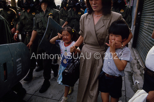 "Seoul, South Korea.June 27, 1987..A mother tries to protect her children from the overpowering tear gas that filled the streets of Seoul during a period of intense political rioting...After two decades of building an economic miracle, in the summer of 1987 tens of thousands of frustrated South Korean students took to the streets demanding democratic reform. ""People Power"" Korean-style saw Koreans from all social spectrums join in the protests...With the Olympics to be held in South Korea in 1988, President Chun Doo Hwan decided on no political reforms and to choose the ruling party chairman, Roh Tae Woo, as his heir. The protests multiplied and after 3 weeks Chun conceded releasing oppositionist Kim Dae Jung from his 55th house arrest and shaking hands with opposition leader Kim Young Sam. Days later he endorsed presidential elections and an amnesty for nearly 3,000 political prisoners. It marked the first initiative of democratic reform in South Korea and the people had their victory."