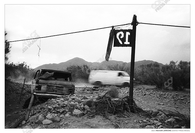"US and Mexico border fence, a suspected ""coyote"" (smugglers) vehicle loaded with passengers passes a wrecked vehicle while traveling on the Mexican side of the border. Cochise County, Arizona, July 2003."