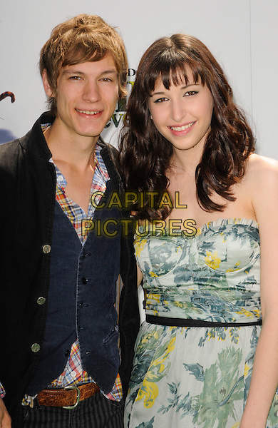 "LANDON PIGG & LUCY SCHWARTZ .arriving at the Los Angeles premiere of Dreamworks Animation's ""Shrek Forever After"" at Gibson Amphitheatre in Universal City, California, .May 16th, 2010.half length blue waistcoat black jacket green print strapless dress  .CAP/ROT.©Lee Roth/Capital Pictures"