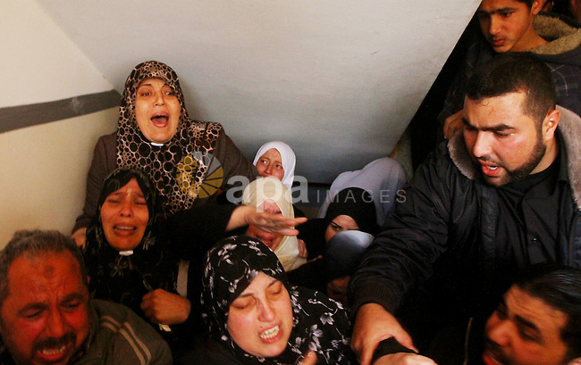 Relative of Palestinians Sobhi al-Batsh, a member of Hamas's armed wing the Ezzedine al-Qassam Brigades, and Issam al-Batsh, a senior member of the Al-Aqsa Martyrs Brigades, mourn at his home during his funeral in Gaza City on December 8, 2011. The two Gaza militants were killed in an Israeli strike, Palestinian medics said, with Israel saying one of them had planned a deadly bombing in Eilat in 2007. Photo by Ashraf Amra