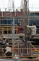 Workers with helmets on scaffolding at the construction site in Madras, India