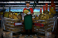 17 year old Deny, a high school student at Kartini Emergency School, holds a durian at a Fresh Fruits and Vegetables division of a foreign franchise Supermarket in Jakarta where he now earns a decent living as a contract worker. The twins recomended Deny to the Supermarket's Director and after passing some stests, he was accepted. Since the early 1990s, twin sisters Sri Rosyati (known as Rossy) and Sri Irianingsih (known as Rian) have used their family inheritance to set up and run 64 schools in different parts of Indonesia, providing primary education combined with practical skills to some of the country's most deprived children.