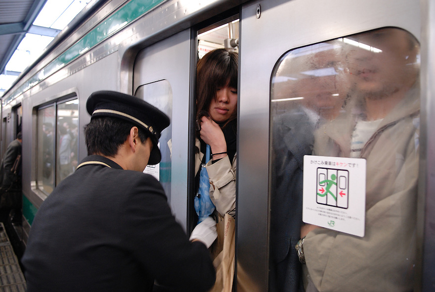 Commuters squeeze onto a train. The guard pushes them in to help the door close. Tokyo has one of the most extensive and efficient transport networks in the world - but also one of the most crowded. Rail companies calculate crowding by percent of standard capacity (ie when all the seats and standing spaces are occupied). Some trains reach 220%+.