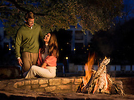 A couple sits in front of a bon fire.
