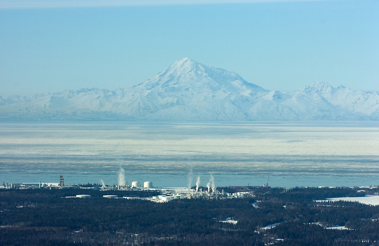 Mount Redoubt volcano looms on the western horizon about 50 miles across an ice-choked Cook Inlet with facilities associated with the oil and natural gas industry in Nikiski and nearby Kenai, Alaska. At left is the Agrium fertilizer plant. Left of center is a liquified natural gas (LNG) plant operated by Conoco-Phillips. At center is a Tesoro refinery.