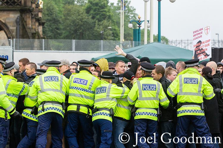 © Joel Goodman - 07973 332324 . 09/06/2012. Rochdale , UK. Police lines push back EDL supporters at the demonstration . The English Defence League ( EDL ) hold a march and rally in Rochdale Town Centre . Photo credit : Joel Goodman