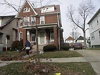 Detroit: downtown, il centro della città. Una villa di mattoni ben tenuta. Una persona fa dei lavori di giardinaggio. Un'auto è parcheggiata nel vialetto.