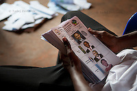 Election worker holds a stack of ballots in a polling station in Kigali, Rwanda. All votes in this stack were for president Paul Kagame. August 9 2010
