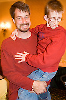 Jonathan Maul says holds on to his father Doug at the Share and Care Network's annual retreat held at the Doubletree Guest Suites Hotel in Boston on May 20, 2006. <br /> <br /> The Share and Care Network was created in 1981 by Pat Cahill when her son Scott was diagnosed with Cockayne Syndrome.  A rare form of dwarfism, Cockayne Syndrome is a genetically determined condition whose symptoms include microcephaly, mental retardation, progressive blindness, progressive hearing loss, premature aging, and a shortened lifespan averaging 18 years.  Those afflicted have distinctive facial features, including sunken eyes, pinched faces, and protruding jaws as well as distinctive gregarious, affectionate personalities.<br /> <br /> Because of the rarity of the condition (1/1,000 live births) and its late onset (characteristics usually begin to appear only after one year), many families and physicians are often baffled by children whose health begins to deteriorate after normal development.  It was partly with this in mind that the Share and Care Network was formed, to promote awareness of this disease as well as to provide a support network for those families affected.  In 1998 it began organizing an annual retreat, which has grown from three families in its inaugural year to more than 30 today.  Although the retreat takes place in the United States, families from as far as Japan arrive for this one weekend out of the year to share information and to support one another.