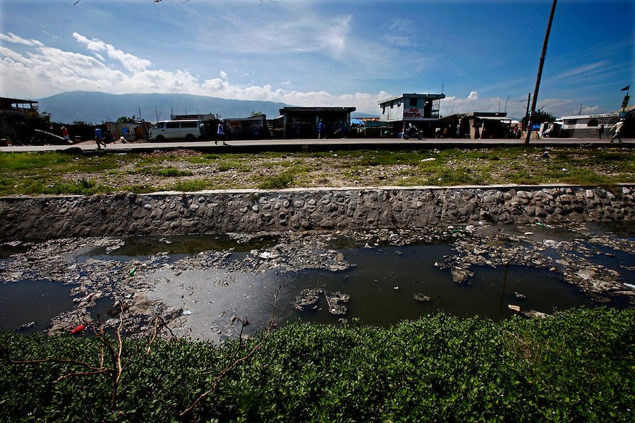 Nov 10, 2010 - Port-au-Prince, Haiti.Residents of the Cite Soleil area of Port-au-Prince, Haiti go about their daily lives just yards away from a river of human waste and garbage on Wednesday, November 10, 2010 as fears of a Cholera outbreak spread through the area just two days after cases of the infection were confirmed in the area, the poorest slum in Haiti's capital. Officials from the Pan American Health Organization warn that Haiti's cholera epidemic, spread primarily through consuming infected water and food, is likely to grow much larger in the wake of Hurricane Tomas.  (Credit Image: Brian Blanco/ZUMA Press)