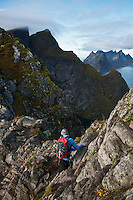 Female hiker climbs rocks on Reinebringen, Lofoten Islands, Norway