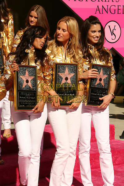 SELITA EBANKS, KAROLINA KURKOVA & ADRIANA LIMA.Victoria's Secret Angels Receive Award of Excellence from Honorary Mayor of Hollywood Johnny Grant in Celebration of the Victoria's Secret 25th Anniversary, Hollywood, California, USA..November 13th, 2007.models full length gold silver metallic star jacket white jeans denim plaque 3/4 .CAP/ADM/RE.©Russ Elliot/AdMedia/Capital Pictures.