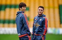 Ki Sung-yueng and Matt Grimes of Swansea City inspect the pitch during the Barclays Premier League match between Norwich City and Swansea City played at Carrow Road, Norwich on November 6th 2015