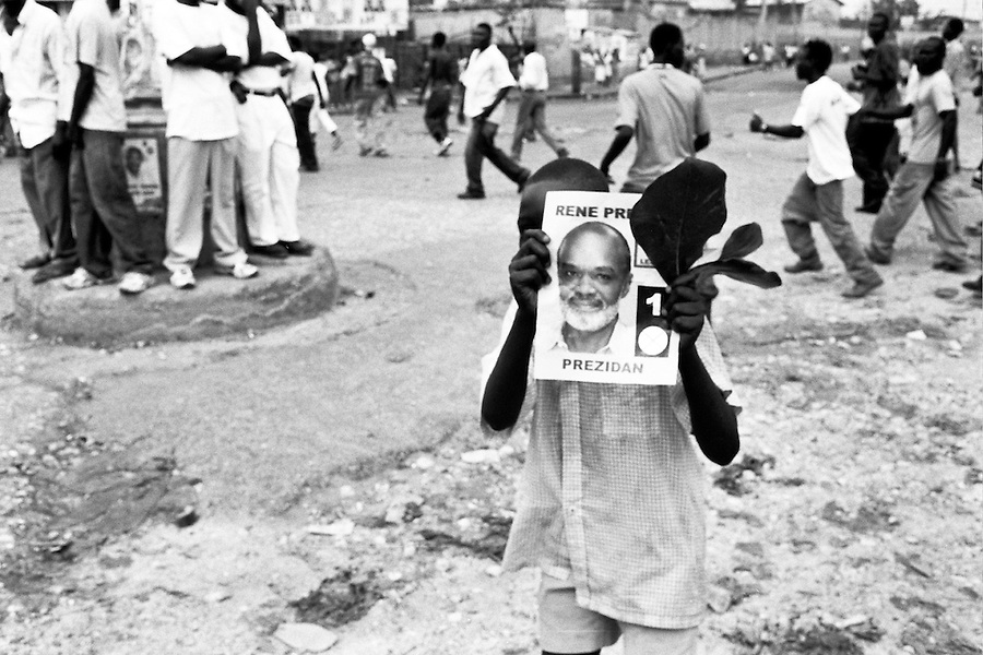 Haitian boy hiding behing a Preval flyer on the day of the elections in Port-Au-Prince.