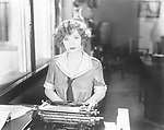 Young woman sitting in front of a typewriter