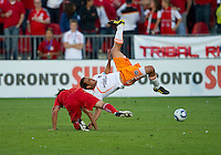 01 July 2010:  Houston Dynamo midfielder Danny Cruz #5 tumbles over Toronto FC defender Nick Garcia #4 during a game between the Houston Dynamo and the Toronto FC at BMO Field in Toronto..Final score was 1-1....