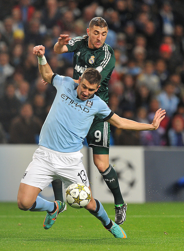 Manchester City's Aleksandar Kolarov  and Real Madrid's Karim Benzema battle for the ball..Football - UEFA Champions League Group D - Manchester City v Real Madrid  - Wednesday 21st November 2012 - Etihad Stadium - Manchester..