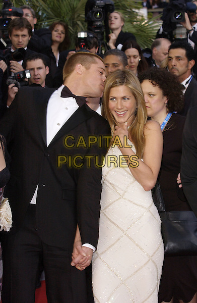 "BRAD PITT & JENNIFER ANISTON.Screening of film ""Troy"" .Cannes Film Festival, .France 13 May 2004..half length kissing head holding hands smiling couple married husband wife long white cream halterneck dress.sales@capitalpictures.com.www.capitalpictures.com.©Capital Pictures"