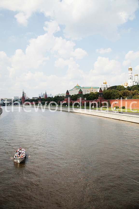 RUSSIA, Moscow. A boat of tourists on the Moscow River with the Kremlin wall on the right side.