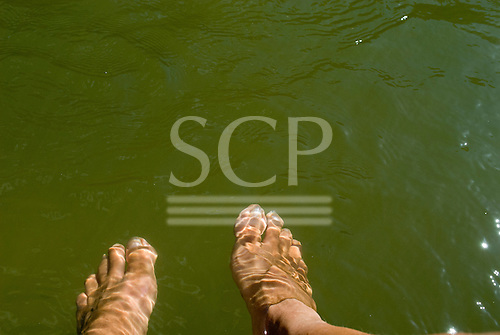 Pará State, Brazil. Xingu River. Sue's feet through the water.