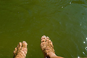 Pará State, Brazil. Xingu River. Sue's feet through the water.