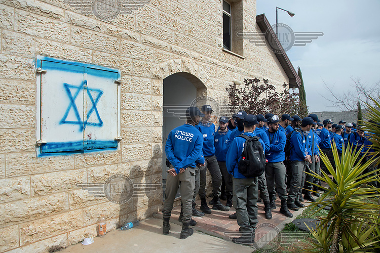 A group of Israeli policemen prepare to evacuate a house in Ofra, one of eight houses in the settlement which the Israeli high court has ruled must be demolished as they are built on privately-owned Palestinian land.