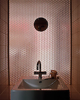 An enamel wash basin within a tiled alcove that has a panel of textured metal across one wall