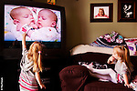 Formerly conjoined twins Abby, left, and Belle Carlsen of Fargo, N.D., delight in watching videos and inspecting photographs of themselves. The Carlsen twins were successfully separated at the Mayo Clinic in Rochester, Minn., on May 12, 2006. The girls will celebrate their 3rd birthday with family and friends this Saturday (Nov. 29, 2008).