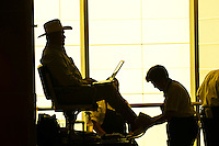 A cowboy hat wearing Texan with laptop gets a shoeshine at George Bush Intercontinental Airport, Houston, Texas USA