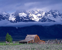 Summer storm light illuminating a barn below the Teton Range; Grand Teton National Park, WY