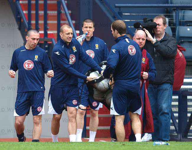 Alan Hutton grabs some balls as he arrives for training