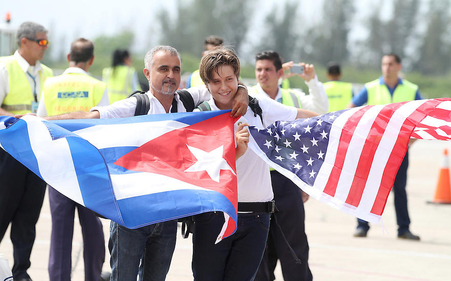 A father holding a Cuban flag, along with his son holding the American flag are seen on the tarmac after stepping off JetBlue's inaugural flight to Santa Clara, Cuba on Wednesday, Aug. 31, 2016. (Donald Traill/AP Images for JetBlue)