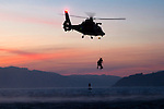 A Coast Guard HH-65 Dolphin helicopter lifts a pair of rescue swimmers out of the waters of San Francisco Bay near Angel Island at sunset. The helicopter and crew, based at U.S. Coast Guard Air Station San Francisco, was on a practice mission to maintain qualifications and search and rescue proficiency.