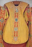 "Chasuble with orfroi embroidery in gold, 1910, with medallion of Saint Louis holding the crown of thorns on a cushion; the crown of thorns with 3 nails; baptismal font with 3 crosses and ""Louis de Poissy"", and banner of Saint Denis, from the Collegiale Notre-Dame de Poissy, a catholic parish church founded c. 1016 by Robert the Pious and rebuilt 1130-60 in late Romanesque and early Gothic styles, in Poissy, Yvelines, France. Saint Louis or King Louis IX of France was born in Poissy in 1214. The Collegiate Church of Our Lady of Poissy was listed as a Historic Monument in 1840. Picture by Manuel Cohen"