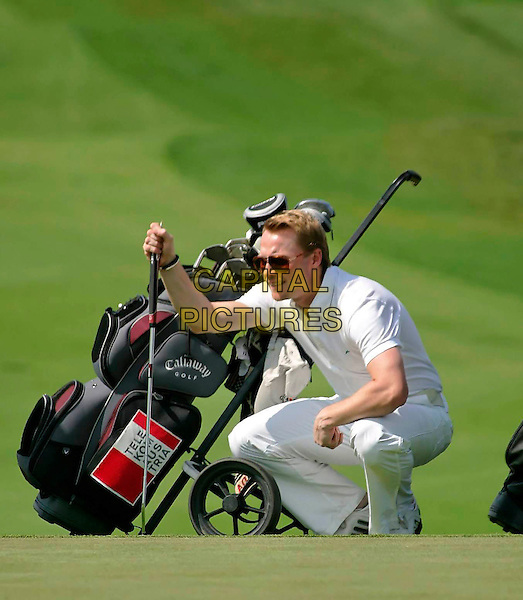 RONAN KEATING.At the Colin Montgomerie Charity Golf Tournament, .Golfclub Fontana, Baden bei Wien, Austria,.4th June 2007..full length game sport club course bending squatting playing bag .CAP/PPG.©Eckharter/People Picture/Capital Pictures. *** Local Caption *** 00310444