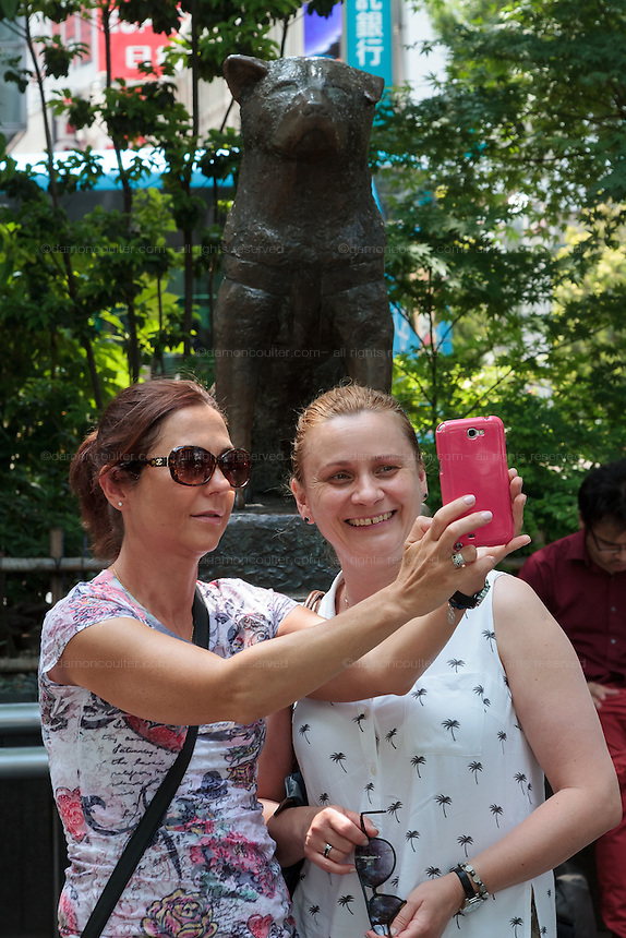 Two western women tourists take a selfie in front of the statue of hachiko in Hachiko Square, Shibuya, Tokyo, Japan. Friday June 10th 2016