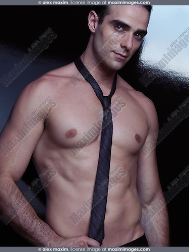 Portrait of a sexy muscular man with bare torso wearing a black necktie