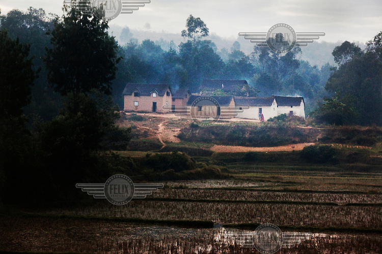 A group of houses crowd together in the highlands, surrounded by forest and rice paddy.